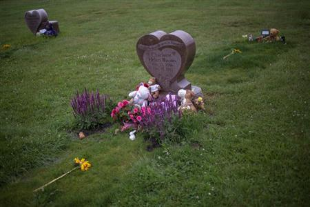 Flowers and stuffed animals are seen at the grave sites of Charlotte Helen Bacon (C), Ana Grace Marquez-Greene (L) and Allison Wyatt, three of 20 school children killed in the December 14 shooting at Sandy Hook Elementary School, at the Newtown Village Cemetery in Newtown, Connecticut June 14, 2013. REUTERS/Adrees Latif