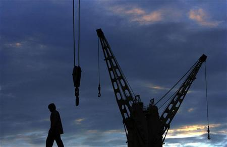 A dock worker walks past a crane on a ship at the port in Mumbai September 6, 2007. REUTERS/Arko Datta/Files