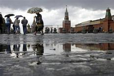 Люди идут под зонтами по Красной площади в Москве, 30 июня 2008 года. Выходные в Москве будут облачными, в воскресенье возможны грозы, прогнозируют синоптики. REUTERS/Denis Sinyakov