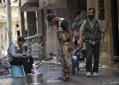 A Free Syrian Army fighter (C) cools himself with water to beat the heat as fellow fighters watch, in Deir al-Zor July 11, 2013. Picture taken July 11, 2013. REUTERS-Khalil Ashawi