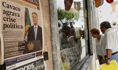 People look at the front pages of newspapers displayed behind the window of a shop in Ericeira village, 40 km (24 miles) north of Lisbon July 11, 2013. REUTERS/Jose Manuel Ribeiro