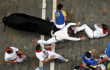A runner is caught between the horns of an El Pilar fighting bull on Estafeta street, before being gored by the same bull, during the sixth running of the bulls of the San Fermin festival in Pamplona July 12, 2013. REUTERS/Susana Vera