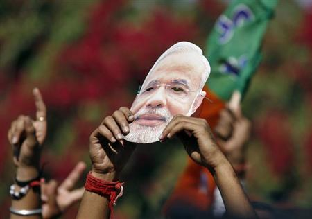 A supporter of Bharatiya Janata Party (BJP) holds a mask of Gujarat state chief minister Narendra Modi during a celebration outside a vote counting centre in Ahmedabad December 20, 2012. REUTERS/Amit Dave/Files