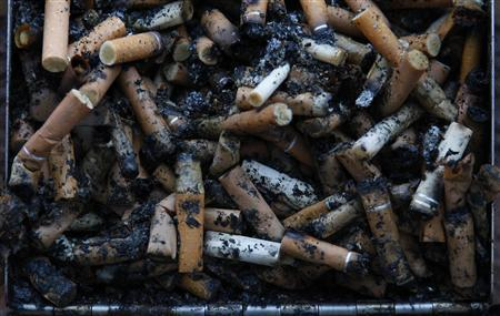Used cigarette butts spill out of a full ashtray on the wall of a shopping centre in Warrington, northern England January 15, 2013. REUTERS/Phil Noble