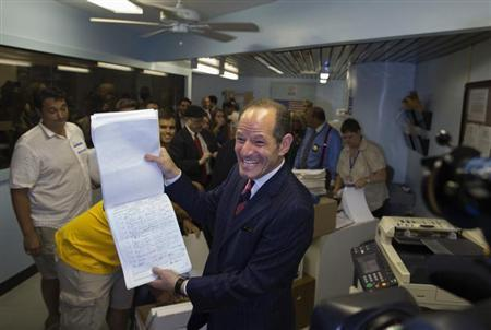 Former New York Governor Eliot Spitzer displays to the media, signatures which he delivered to the board of elections office, in New York July 11, 2013. REUTERS/Eric Thayer