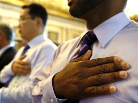 Herbert Crooks (Panama) (R) says the Pledge of Allegiance after he swears in as United States citizen during a Special Naturalization Ceremony for 30 U.S. citizen candidates in the Cash Room at the U.S. Treasury Department in Washington, July 3, 2013. REUTERS/Larry Downing