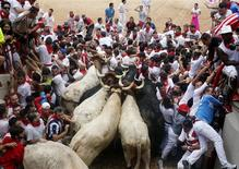 Runners get trapped with Fuente Ymbro fighting bulls and steer in a stampede at the entrance to the bull ring during the seventh running of the bulls of the San Fermin festival in Pamplona July 13, 2013. REUTERS/Josu Santesteban