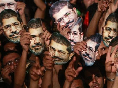 Members of the Muslim Brotherhood and supporters of deposed Egyptian President Mohamed Mursi hold up masks of him as they gather at the Rabaa Adawiya square, where they are camping, in Cairo July 12, 2013. REUTERS/Mohamed Abd El Ghany