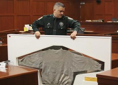 A Seminole County Sheriff's deputy carries Trayvon Martin's shirt as trial evidence is moved out of the courtroom in Sanford, Florida July 13, 2013 during the trial of George Zimmerman in the shooting death of Trayvon Martin. REUTERS-Joe Burbank-Pool