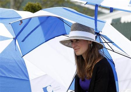 Martina Hingis takes shelter under an umbrella as rain falls during the Tennis Hall of Fame induction ceremony in Newport, Rhode Island July 13, 2013. REUTERS/Jessica Rinaldi