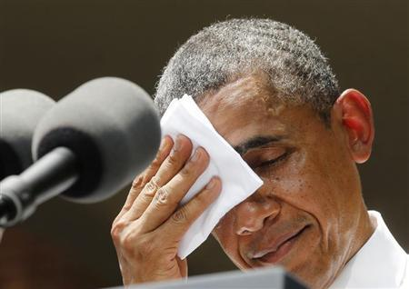 U.S. President Barack Obama pauses and wipes his face as he speaks about his vision to reduce carbon pollution while preparing the country for the impacts of climate change while at Georgetown University in Washington, June 25, 2013. REUTERS/Larry Downing