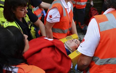 An unidentified 23-year-old Australian woman is taken away to the hospital after getting gored by a Miura fighting bull during the last running of the bulls of the San Fermin festival in Pamplona July 14, 2013. REUTERS/Ivan Urquizu