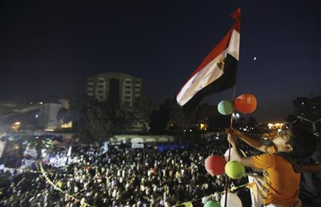 A boy holds an Egyptian flag together with members of the Muslim Brotherhood and supporters of deposed Egyptian President Mohamed Mursi at the Rabaa Adawiya square, where they are camping, in Cairo July 12, 2013. REUTERS/Amr Abdallah Dalsh