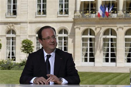 French President Francois Hollande speaks with journalists after a television interview in the garden of the Elysee Palace, following the traditional Bastille day military parade in Paris July 14, 2013. REUTERS/Philippe Wojazer