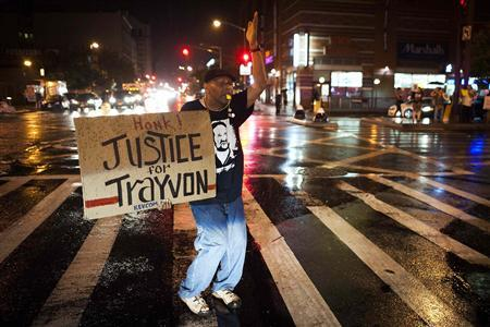 Will Reese holds a protest sign in response to the acquittal of George Zimmerman in the Trayvon Martin trial, in the Harlem neighborhood of New York, July 14, 2013. REUTERS/Keith Bedford