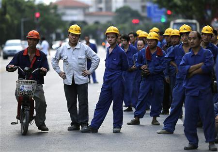 Construction workers wait for a bus after their workday at Pudong financial district in Shanghai July 8, 2013. China's resolve to revamp its economy for the long-term good will be tested this month when a slew of data show growth is grinding towards a 23-year low, with no recovery in sight. REUTERS/Carlos Barria