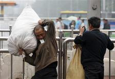 A migrant worker holding a ticket in his mouth carries his luggage at Beijing railway station June 7, 2013. REUTERS/Kim Kyung-Hoon