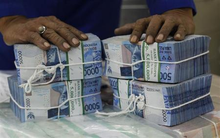 A worker prepares bundles of rupiah bank notes in Bank Mandiri in Jakarta July 9, 2013. REUTERS/Supri