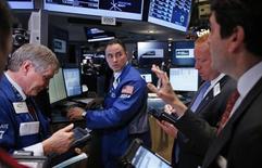 Трейдеры на торгах Нью-Йоркской фондовой биржи 20 мая 2013 года. Американские фондовые рынки поднялись в пятницу благодаря сильной квартальной отчетности банков и завершили ростом прошлую неделю. REUTERS/Mike Segar