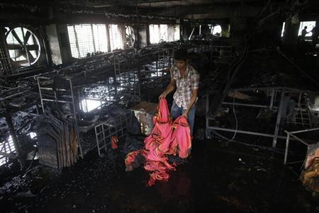 A garment worker inspects a factory belonging to Tung Hai Group, a large garment exporter, after a fire in Dhaka May 9, 2013. REUTERS/Andrew Biraj