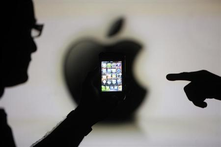 Men are silhouetted against a video screen with an Apple logo as they pose with an Apple iPhone 4 smartphone in this photo illustration taken in the central Bosnian town of Zenica, May 17, 2013. REUTERS/Dado Ruvic/Files