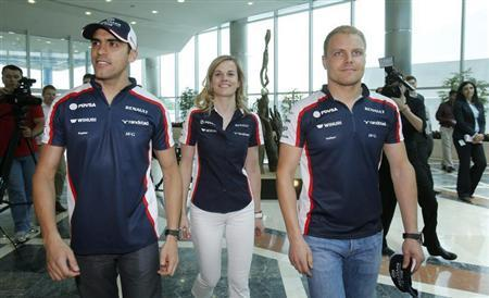 Williams Formula One drivers Pastor Maldonado (L) of Venezuela and Valtteri Bottas (R) of Finland and test-driver Susie Wolff of Britain walk during a visit to the Aspire sports academy in Doha April 22, 2013. REUTERS/ Fadi Al-Assaad