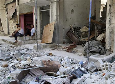 Men sit along a damaged street filled with debris in Harasta area in Damascus July 14, 2013. REUTERS/Mohamed Abdullah