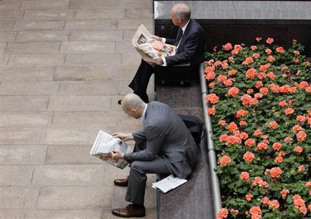 Two men read newspapers in the financial district of Canary Wharf in London August 17, 2011. REUTERS/Kevin Coombs