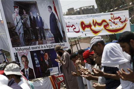 Members of the Muslim Brotherhood and supporters of deposed Egyptian President Mohamed Mursi perform afternoon prayers near a defaced poster of U.S. President Barack Obama, U.N. Secretary-General Ban Ki-moon and the head of Egypt's armed forces General Abdel Fattah al-Sisi at the Rabaa Adawiya square, where they are camping, in Cairo, July 15, 2013. REUTERS/Amr Abdallah Dalsh