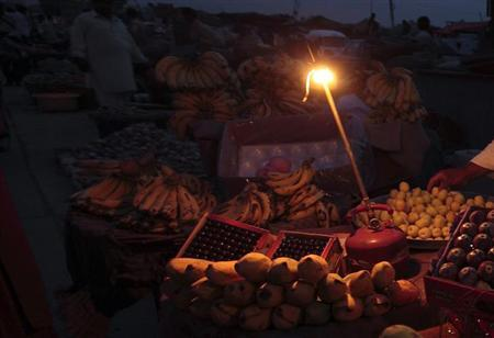 A gas-lamp is seen at a fruit stall during a power outage in Rawalpindi June 3, 2013. REUTERS/Faisal Mahmood/Files