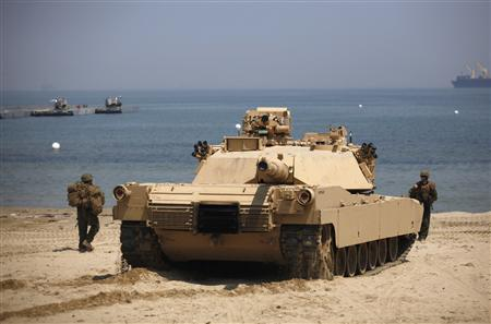 A U.S. marine soldier directs a M1A1 battle tank during the Combined Joint Logistics Over The Shore (CJLOTS) exercise, as a part of the annual joint U.S. and South Korean exercise ''Foal Eagle'', at a seashore in Pohang, about 370 km (231 miles) southeast of Seoul April 22, 2013. REUTERS/Kim Hong-Ji