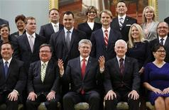 Canadian Prime Minister Stephen Harper (front row, C) gestures while posing with his cabinet ministers and Canadian Governor General David Johnston during a ceremony at Rideau Hall in Ottawa July 15, 2013. REUTERS/Chris Wattie