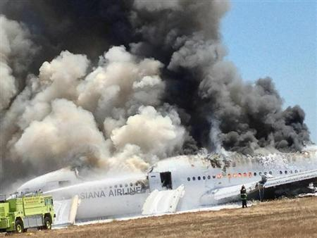 Asiana Airlines Boeing 777 is engulfed in smoke on the tarmac after a crash landing at San Francisco International Airport in California July 6, 2013 in this handout photo provided by passenger Eugene Anthony Rah, released to Reuters on July 8, 2013. REUTERS/Eugene Anthony Rah/Handout via Reuters