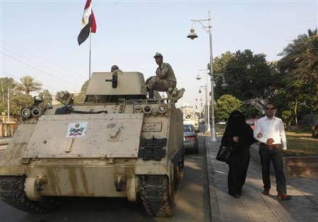 A couple walks past an Egyptian soldier keeping watch from atop a military vehicle in front of the presidential palace in Cairo July 14, 2013. REUTERS/Asmaa Waguih