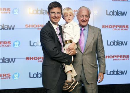 Executive chairman of Loblaw Companies Limited Galen G Weston (L) holds his son Graydon, as they pose with W. Galen Weston (R) in Toronto, July 15, 2013. REUTERS/Mark Blinch