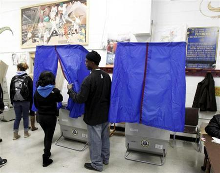 A poll worker assists a voter with the voting booth curtain before voting during the U.S. presidential election at the Penrose recreation center in Philadelphia, Pennsylvania, November 6, 2012. REUTERS/Tim Shaffer