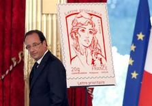 French President Francois Hollande unveils the new official Marianne post stamp at the Elysee Palace during the Bastille Day celebrations in Paris, July 14, 2013. REUTERS/Francois Mori/Pool