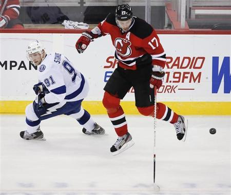 New Jersey Devils right wing Ilya Kovalchuk (17) leaps over the puck in front of Tampa Bay Lightning center Steven Stamkos (91) in the third period of their NHL hockey game in Newark, New Jersey, February 7, 2013. REUTERS/Ray Stubblebine