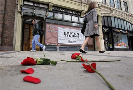 Flowers lay on the sidewalk at the site of the first explosion as people walk along Boylston Street after the street reopened to the public for the first time since the Boston Marathon bombings in Boston, Massachusetts April 24, 2013. REUTERS/Jessica Rinaldi