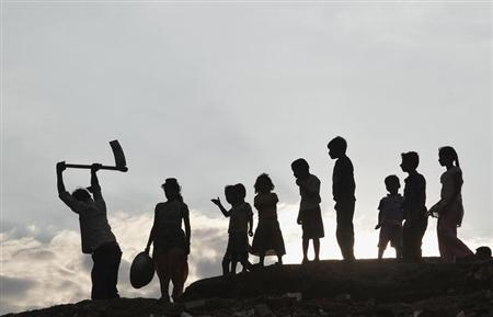 Children stand next to a labourer working on the banks of river Ganges as they are silhouetted against the setting sun in Allahabad July 3, 2013. REUTERS/Jitendra Prakash
