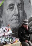 Женщина-продавец на фоне изображения долларовой купюры в Киеве 19 ноября 2012 года. Курс доллара стабилен на фоне ожиданий, что ФРС первой из основных центробанков начнет ужесточать политику. REUTERS/Anatolii Stepanov