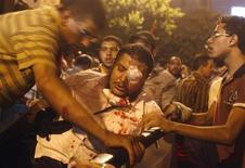 Сторонники президента Мохамеда Мурси помогают своему раненому товарищу во время массовых протестов в Каире 16 июля 2013 года. Как минимум 22 человека получили травмы в ходе новых массовых столкновений между полицией и сторонниками свергнутого президента-исламиста Мохамеда Мурси в столице Египта в ночь на вторник, сообщило государственное новостное агентство MENA. REUTERS/Asmaa Waguih