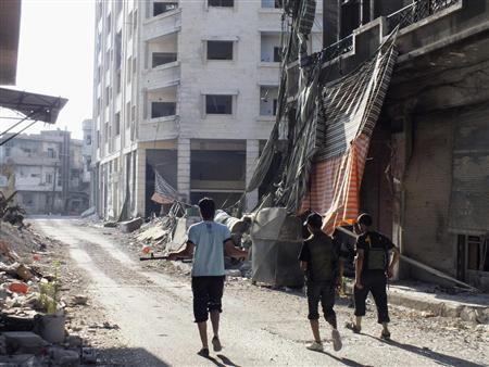 Members of the Free Syrian Army walk along a damaged street filled with debris in the besieged area of Homs July 13, 2013. REUTERS/Yazan Homsy
