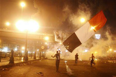 Supporters of Egyptian president Mohamed Mursi waving a national flag run from tear gas during clashes with riot police at the 6th October Bridge in the Ramsis square area in central Cairo July 15, 2013. REUTERS/Asmaa Waguih