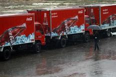 A woman walks near Coca-Cola vehicles during rainfall in Yangon June 4, 2013. REUTERS/Soe Zeya Tun