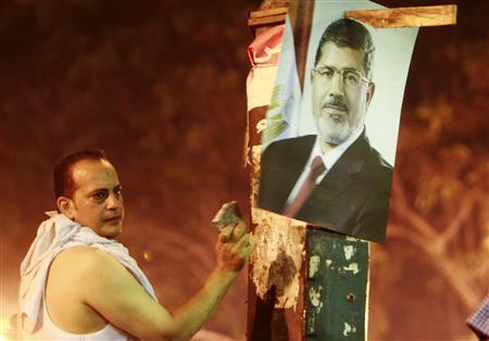 A supporter of deposed Egyptian President Mohamed Mursi knocks a stone on a pillar to alert other supporters that riot policemen are fire tear gas on them on the Sixth of October Bridge over the Ramsis square area in central Cairo July 15, 2013. REUTERS/Mohamed Abd El Ghany