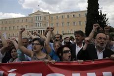 Люди на акции протеста против планов властей в Афинах 16 июля 2013 года. Массовая забастовка проходит в Греции во вторник в знак протеста против планов правительства уволить тысячи работников бюджетной сферы страны. REUTERS/John Kolesidis
