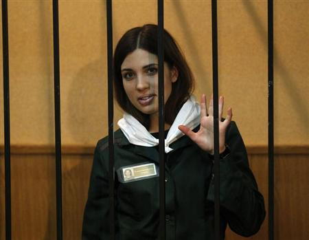 Pussy Riot band member Nadia Tolokonnikova waves from a holding cell during a court hearing in the town of Zubova Polyana April 26, 2013. REUTERS/Mikhail Voskresensky/Files