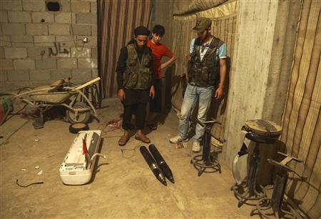 Members of the Free Syrian Army check an improvised mortar shell in Deir al-Zor July 15, 2013. Picture taken July 15, 2013. REUTERS/Khalil Ashawi
