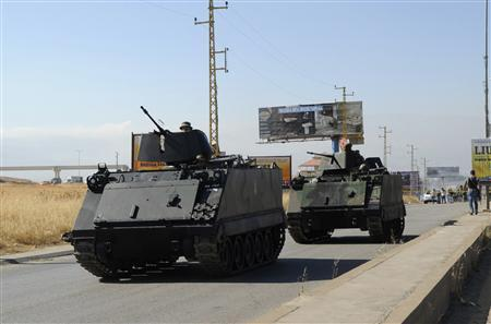 Lebanese Army soldiers on their armoured carriers secure the site of a roadside bomb attack on a highway linking the town of Majdal Anjar to the Masnaa border crossing near the Lebanese-Syrian border July 16, 2013. REUTERS/Stringer